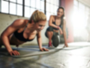 Woman Doing Pushups With Trainer In Gym