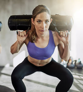 Woman Doing Squats With Shoulder Weights