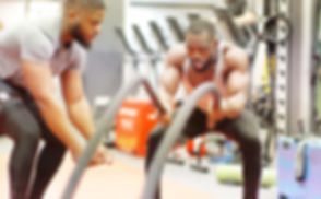 Man Working Out With Ropes With Trainer In Gym