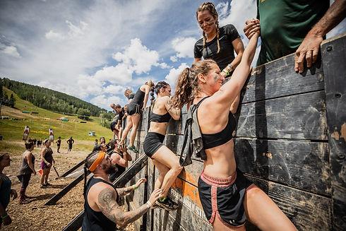 Tough Mudder Course Participants Climbing Over Wall