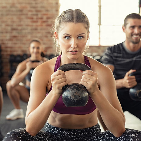 Woman With Kettlebell Squatting In Class