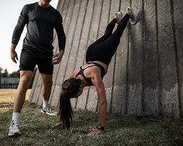 Woman And Trainer Doing Upside Down Pushup Outside