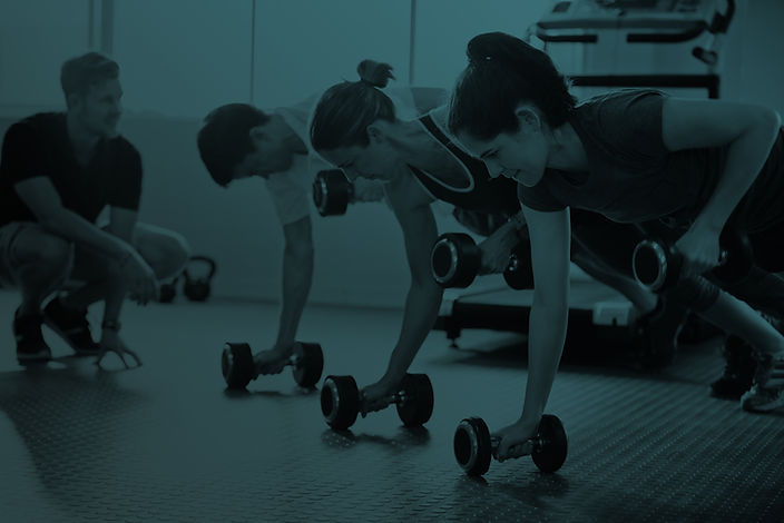 Workout Class Lifting Weights On Floor With Trainer