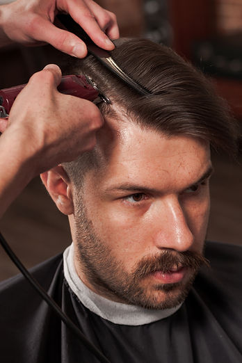the-hands-of-barber-making-haircut-to-young-man-in-P47LB4H.jpg
