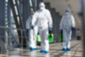 People in virus protective suits and mas