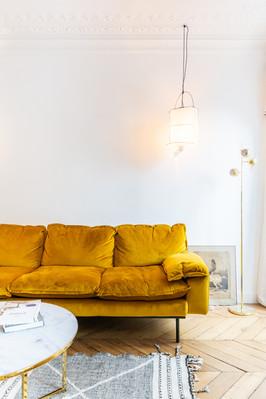 détail salon avec canapé ocre et suspension maison de vacances