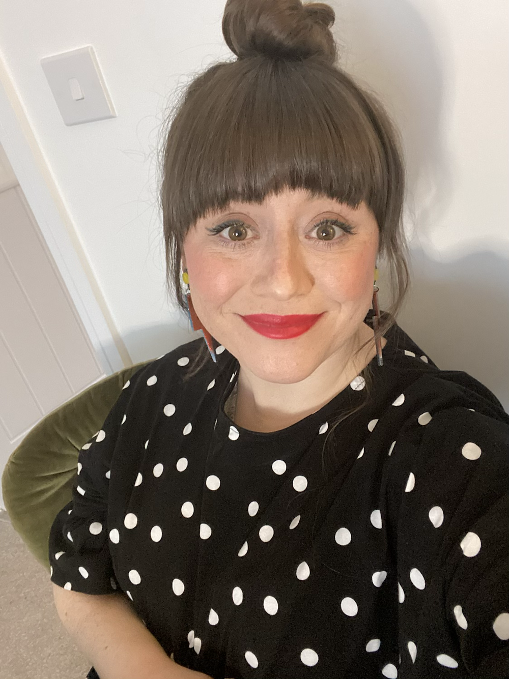A close up selfie of Lorna, a white woman with brown hair tied up in a top knot. She has a heavy fringe. She is wearing make up, a polka dot dress, lightening bolt earrings and is smiling directly at the camera.