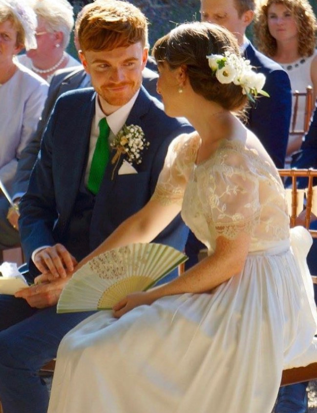 An image of Lorna and her husband on their wedding day. He is smiling at her lovingly and holding her hand.
