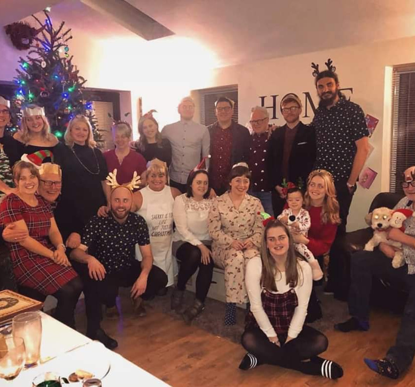 An image of Lorna and her extended family gathered together on Christmas Day. They are all standing/sitting with their arms around one another and smiling.