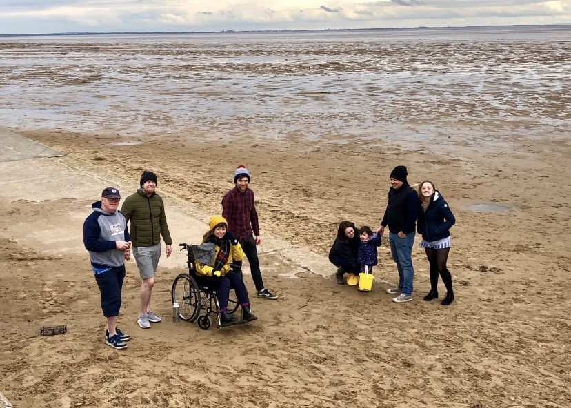 A photo of Lorna and some of her family members on a beach. Lorna is sitting in her wheelchair and they are all playing a game of boules.