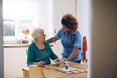 Care worker giving an old lady her dinner in her home.jpg