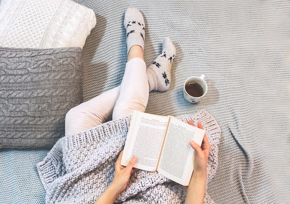Woman reading and relaxing with tea before bedtime.