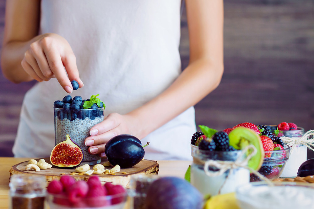 Woman preparing a healthy breakfast with fruit.