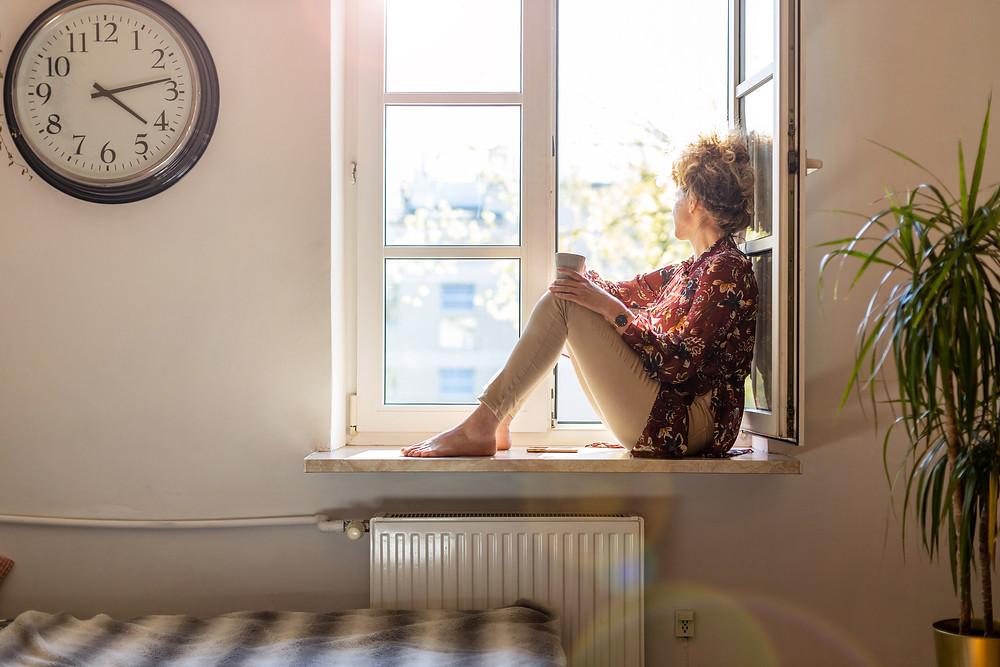 women looking out window feeling like she's lost her rhythm