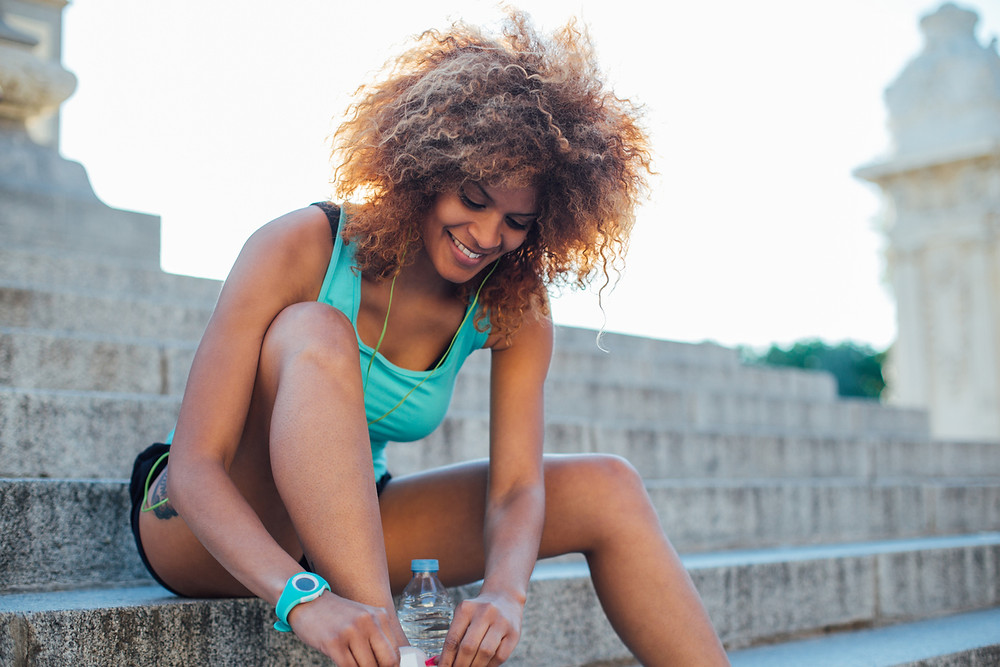 Woman lacing her shoes before a cardio workout.