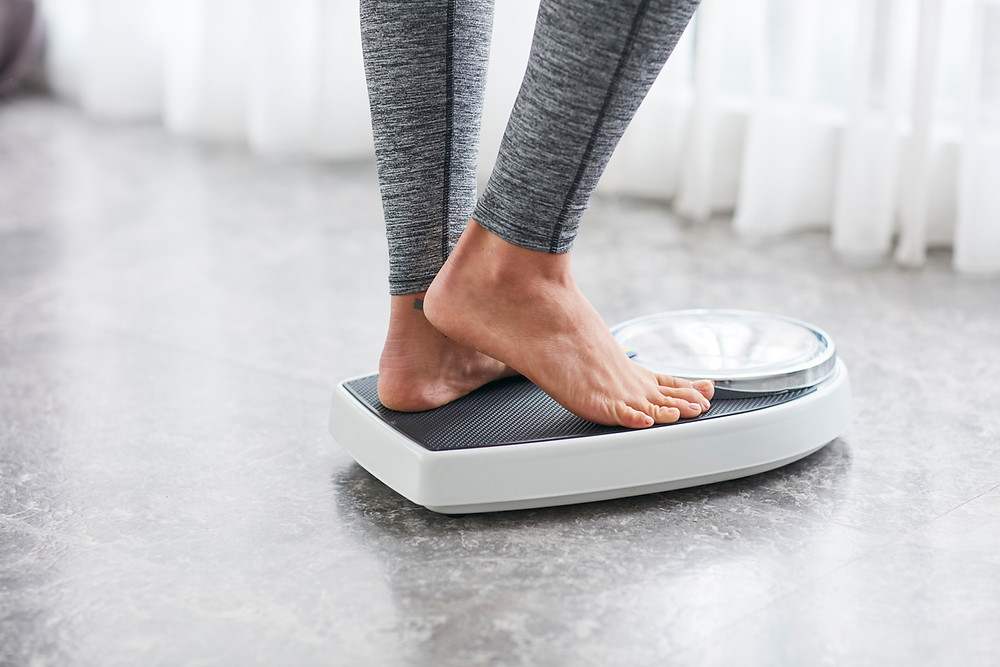 Woman weighing herself after sleeping.