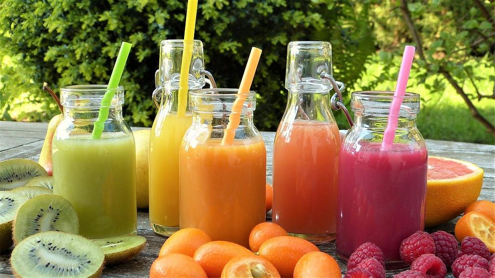 diversos sucos naturais em garrafas de vidro