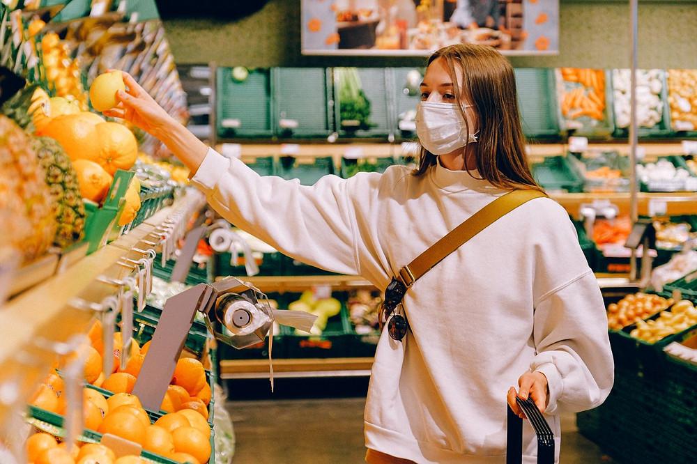 mulher dentro de um mercado escolhendo uma fruta