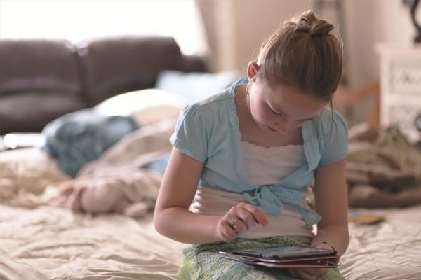 menina usando tablet sentada na cama