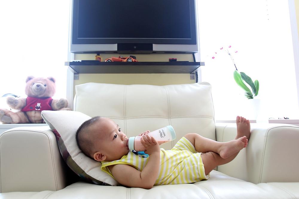 bebê deitado no sofá tomando uma mamadeira