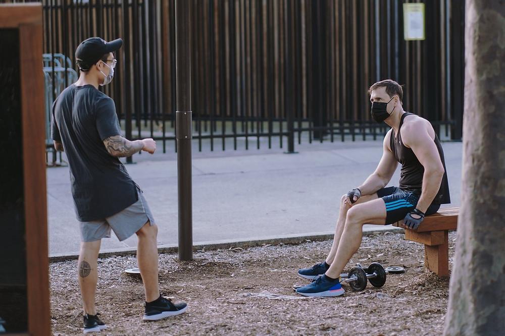 dois homens em um parque conversando de máscara