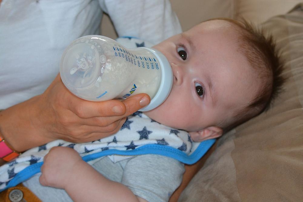 bebê no colo da mãe tomando uma fórmula infantil na mamadeira