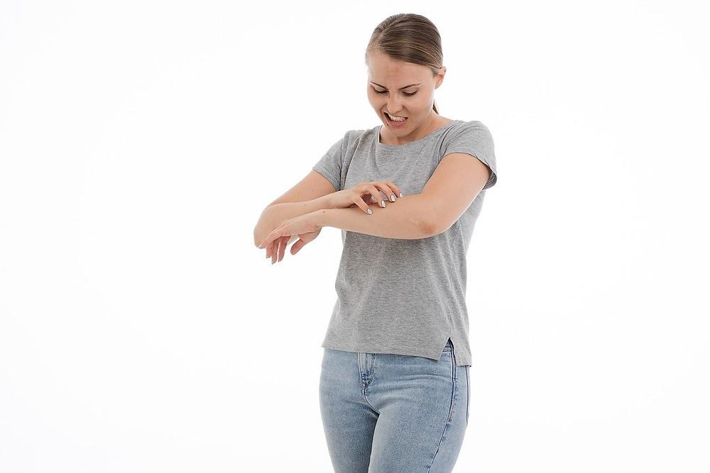 mulher com alergia coçando o braço