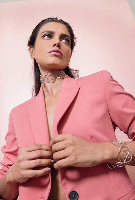 olympic neckpiece and bracelet in sterling silver shot with a model wearing a salmon co-ord set