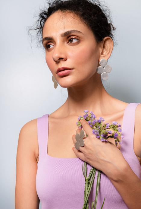 Honeycomb like earrings shot on a model wearing a purple dress with lavender flowers