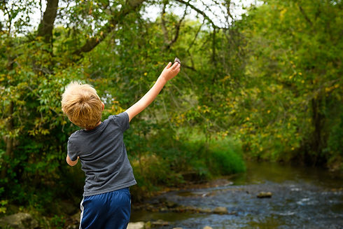 Kid throwing rock into creek CityofRoche