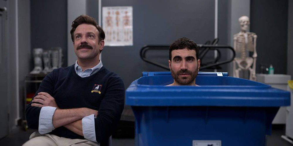 Foils Ted Lasso and Roy Kent radiate their qualities of relentless positivity and extreme irritability.
