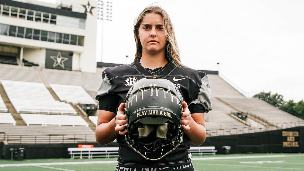 """Sarah Fuller holds football helmet reading """"Play Like A Girl."""""""