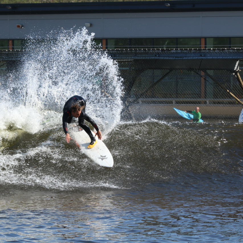 Surfing at Surf Snowdonia on a Puravida Surfboard wearing Solite Surf Wetsuit boots
