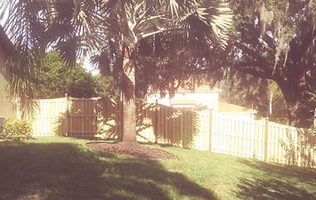 6' Vertical Shadow Box Rackable Wood Fence Panels Scoop Top With French Gothic Posts following a radical down hill slope.