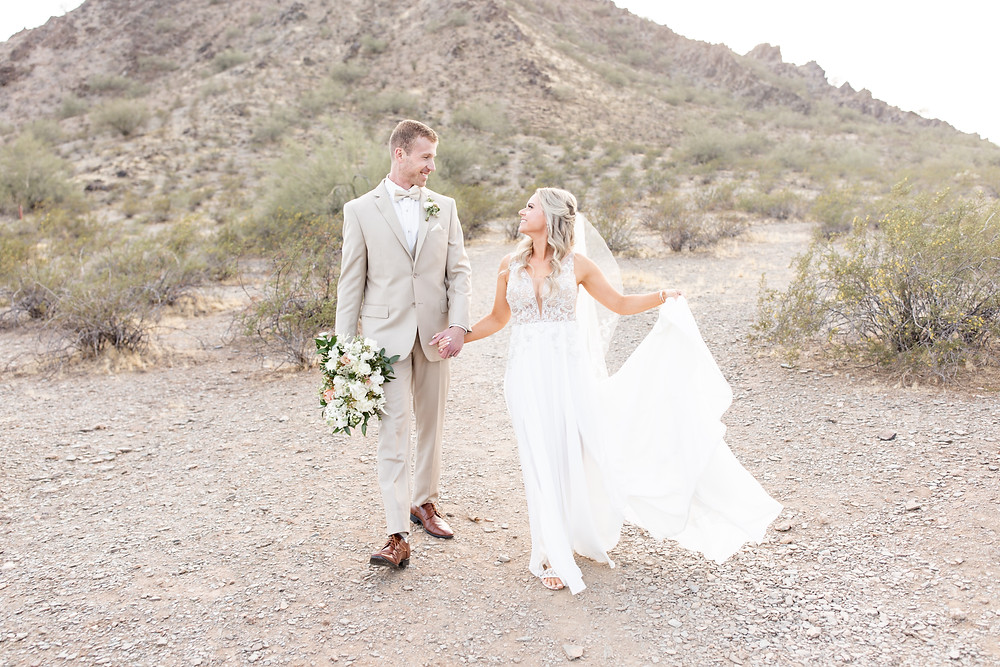 Real wedding couple in tan suit and ivory gown with desert backdrop