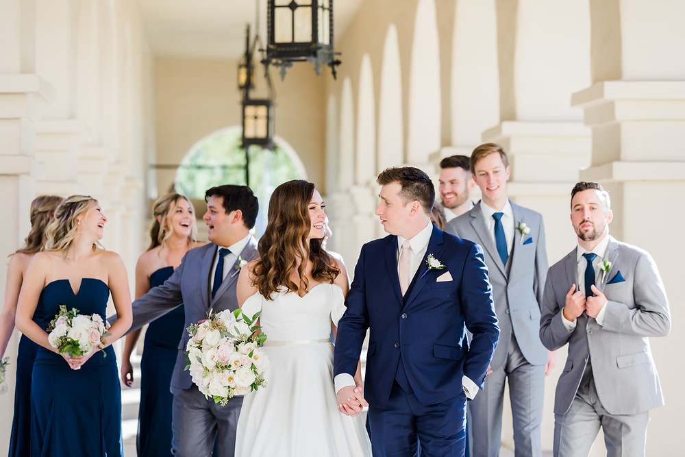 Navy groom suit with grey groomsmen suits and navy bridesmaid dresses