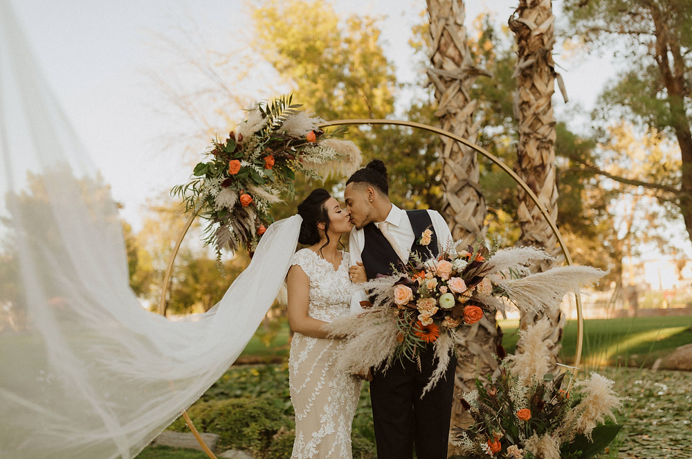 Couple in ivory lace gown and blue suit with floral backdrop