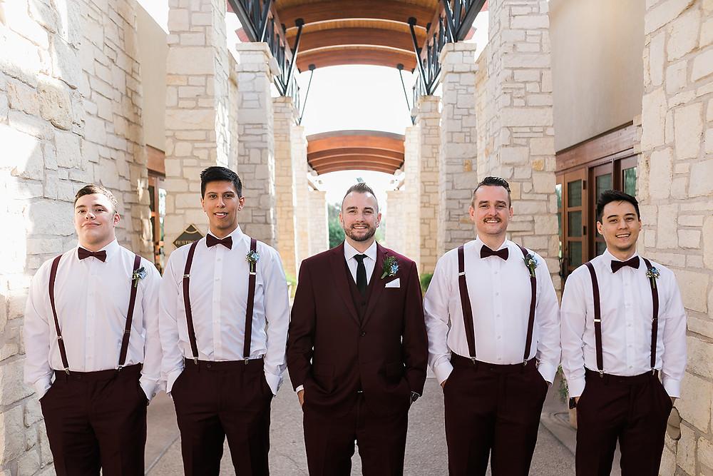 Burgundy suit for groom and suspenders for groomsmen at Wedgewood Ocotillo