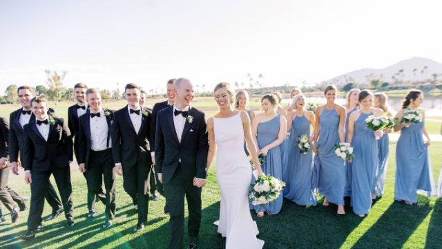 Bridal party in classic black tuxedos in our premium styles and dusty blue bridesmaid dresses
