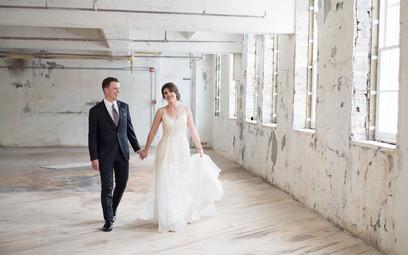Bride & groom walking in warehouse