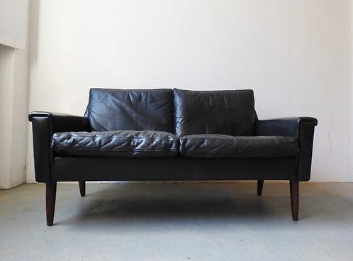 Mid-century Danish black leather sofa with rosewood legs