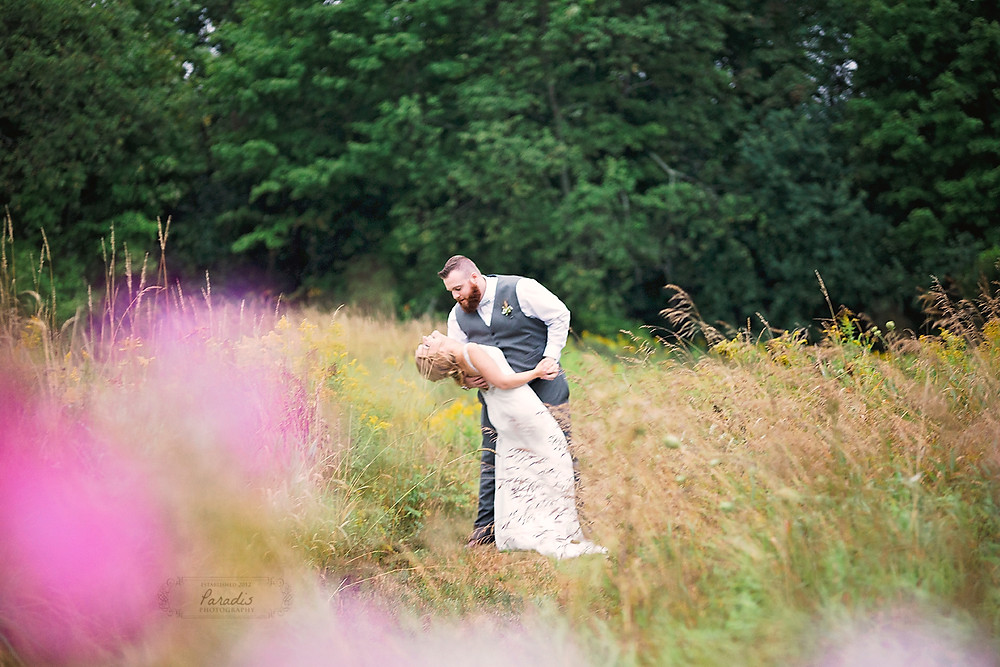 Groom dancing and dipping his bride in a field