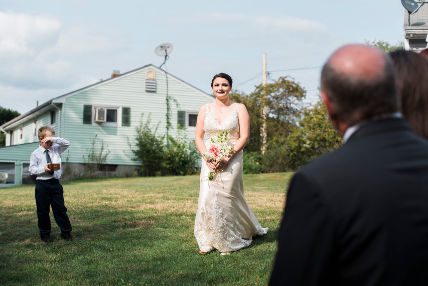 Bride coming down the aisle in a backyard wedding with ring bearer off to the side