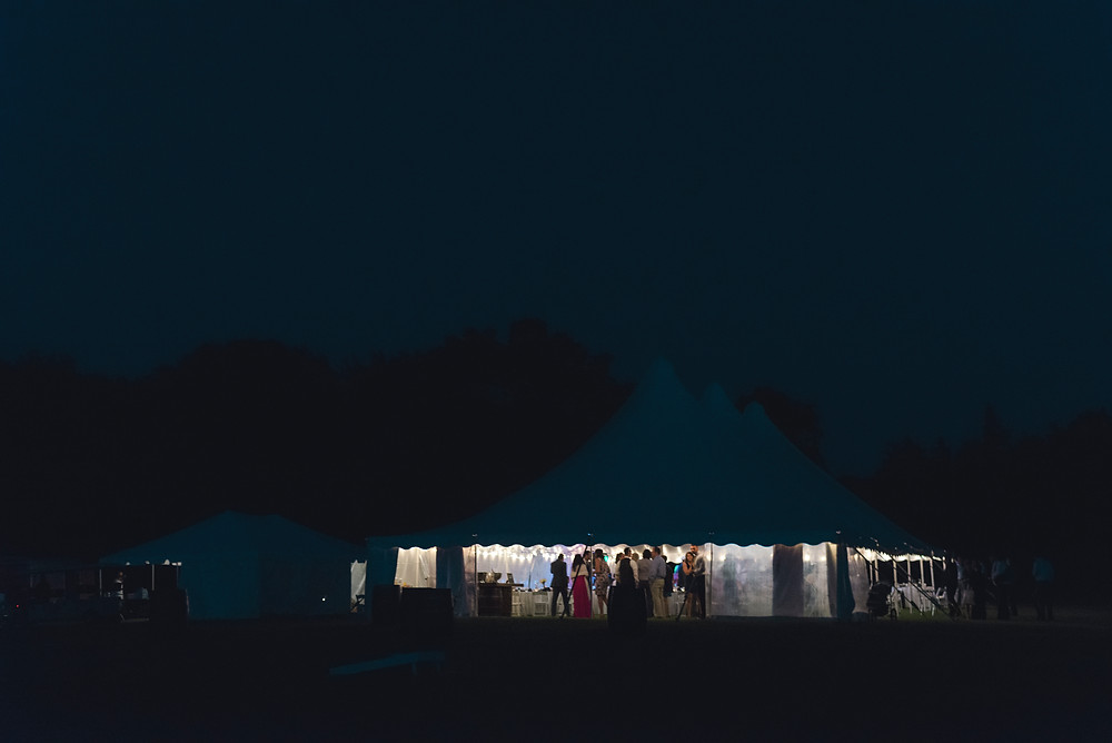 Lit wedding tent in the night full of people