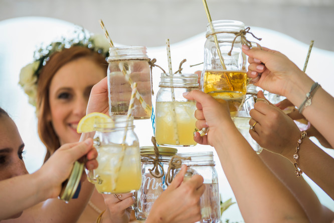 Hands holding glass mugs of lemonade