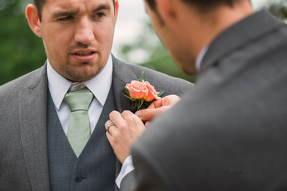 Best man pinning the boutonniere on the groom