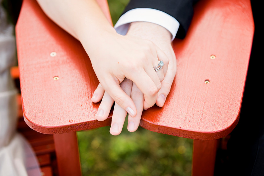 Holding hands showing wedding and engagement rings on the arm of red Adirondack chairs