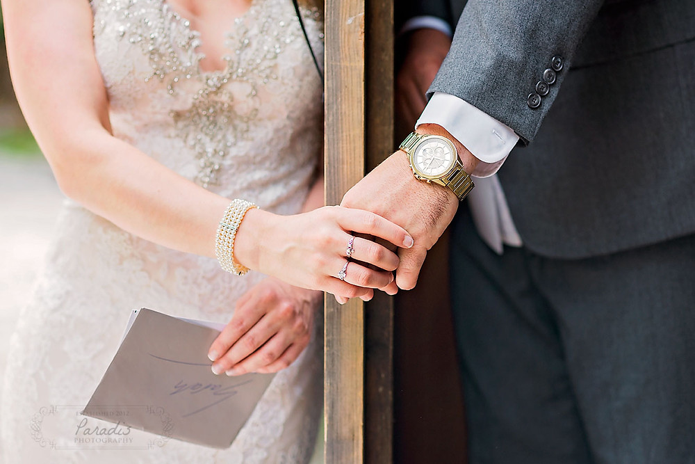 Bride and Groom hold hands and exchange letters before their wedding ceremony