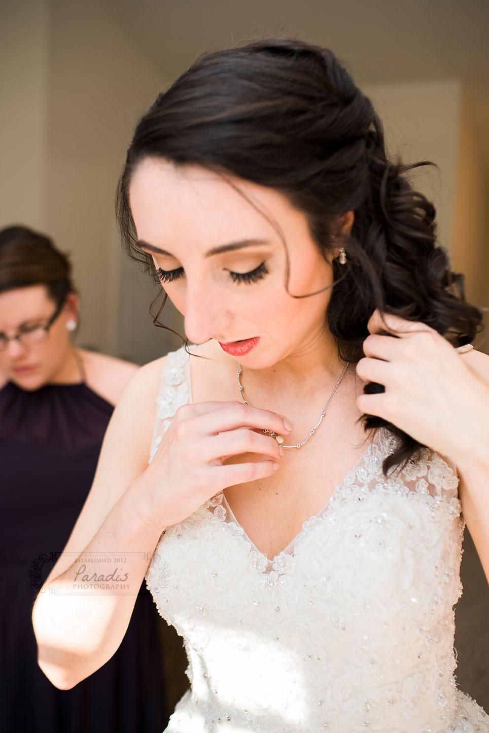 bride adjusting necklace before her maine wedding