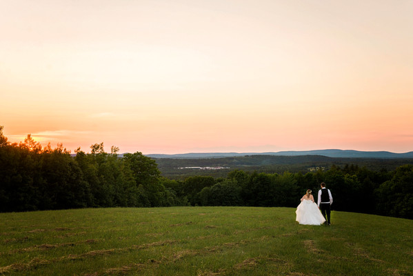 Bride and groom walking away in a field at sunset